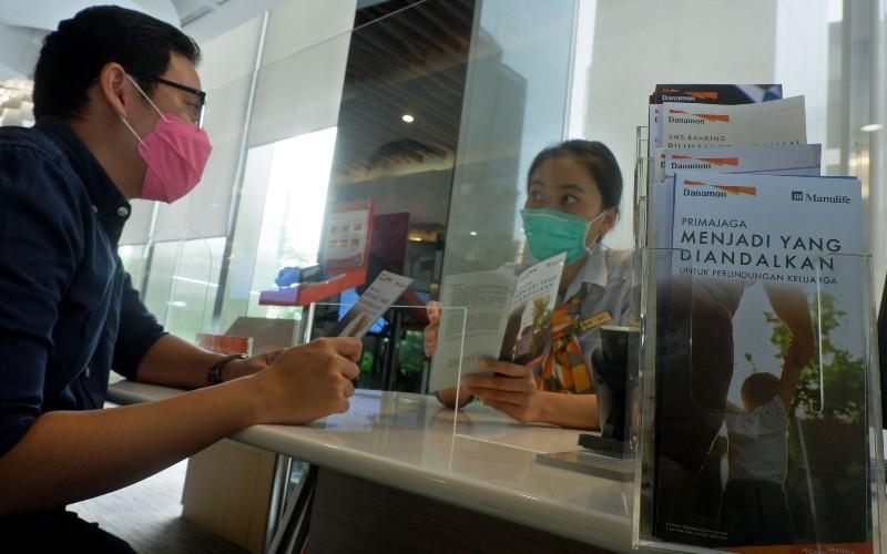 Karyawati memberikan penjelasan kepada nasabah di salah satu kantor PT Bank Danamon Indonesia Tbk. di Jakarta, Selasa (28/4). Bank Danamon dan PT Asuransi Jiwa Manulife Indonesia (Manulife Indonesia) memperkuat kerja sama bancassurance hingga 2036 untuk memenuhi kebutuhan keuangan individu, keluarga, dan pelaku usaha. Hingga 13 April 2020, Manulife telah membayar klaim nasabah sekitar Rp1,6 miliar terkait dengan pandemi Covid-19 - Bisnis/Nurul Hidayat