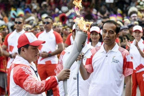 Presiden Joko Widodo (kanan) menyerahkan api obor Asian Games kepada Ketua INASGOC Erick Thohir saat Torch Relay Asian Games 2018 di Istana Merdeka, Jakata, Jumat (17/8/2018). - ANTARA/Hafidz Mubarak A