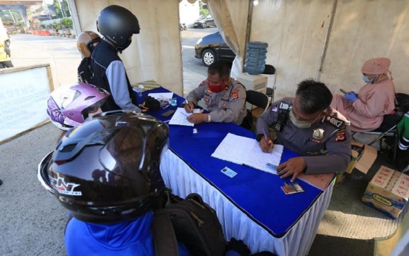 Petugas polisi mendata warga yang keluar masuk Kota Bandung selama PSBB Bandung Raya di salah satu check point. - Bisnis/Dea Andriyawan