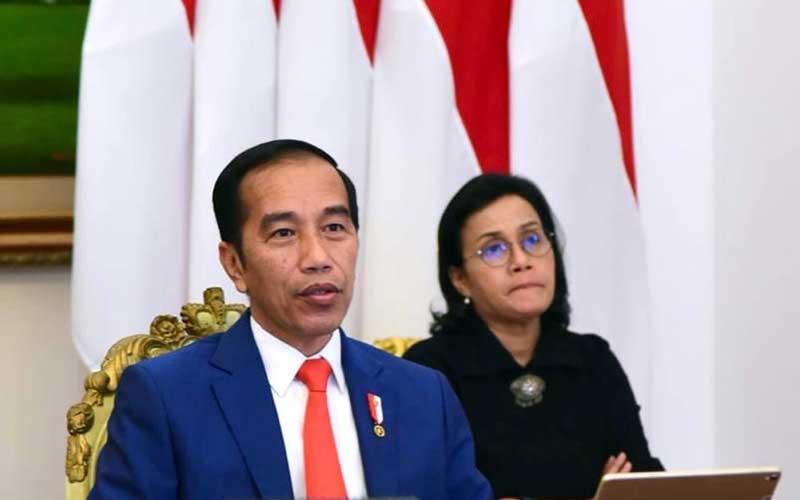 Presiden Joko Widodo (kiri) didampingi Menteri Keuangan Sri Mulyani Indrawati (kanan) saat mengikuti KTT Luar Biasa G20 secara virtual dari Istana Kepresidenan Bogor, Kamis (26/3 - 2020). KTT tersebut membahas upaya negara/negara anggota G20 dalam penanganan COVID/19. Biro Pers dan Media Istana