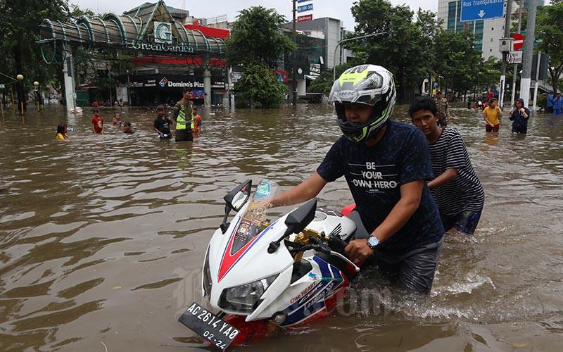 Warga melintasi banjir yang menggenangi Jalan Panjang, Kebon Jeruk, Jakarta, Selasa (25/2/2020)./Bisnis - Eusebio Chrysnamurti