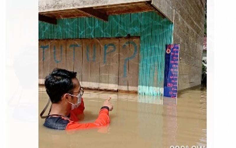 Seorang petugas BPBD Kabupaten Barito Utara tengah mengukur ketinggian muka air terkait banjir di empat kelurahan terdampak pada Rabu (29/4/2020) pagi. - Dok. BNPB
