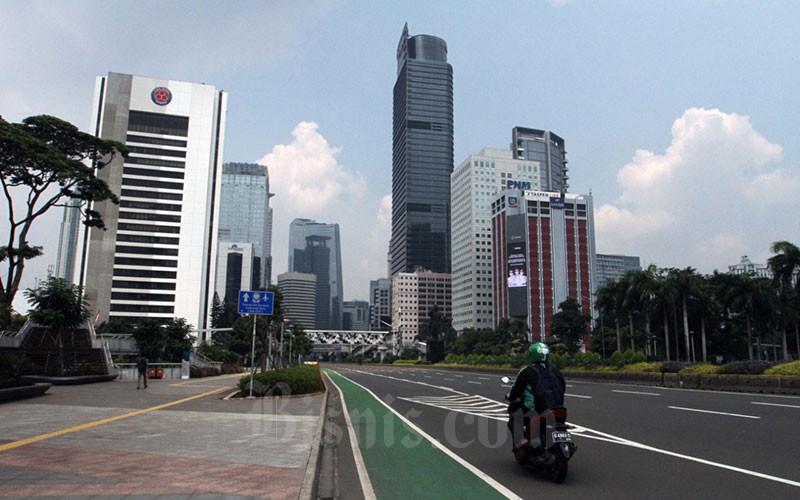 Kendaraan melintas di Jalan Jendral Sudirman yang lengang di Jakarta,Jumat (10/4/2020). - Bisnis/Dedi Gunawan