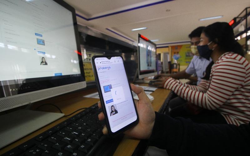Petugas mendampingi warga yang melakukan pendaftaran calon peserta Kartu Prakerja di LTSA-UPT P2TK di Surabaya, Jawa Timur, Senin (13/4/2020). - ANTARA FOTO/Moch Asim
