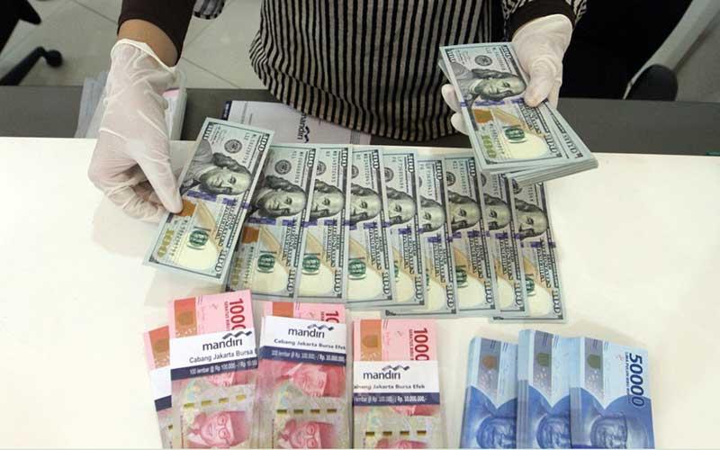 Karyawati bank menata uang dolar AS dan rupiah di kantor cabang PT Bank Mandiri Tbk. di Jakarta, Rabu (22/4/2020). - Bisnis/Dedi Gunawan
