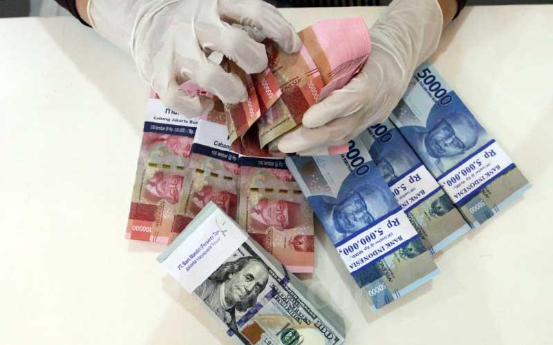 Karyawati bank menata uang dollar dan rupiah di kantor cabang PT Bank Mandiri Tbk. di Jakarta, Rabu (22/4/2020). Bisnis - Dedi Gunawan