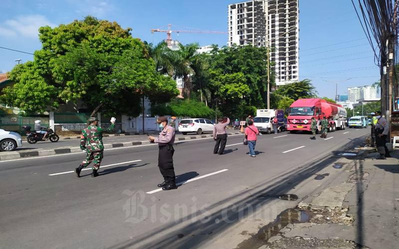 Petugas gabungan dari kepolisian, TNI dan Satpol PP memantau pengendara yang melintas di depan Kantor Polisi Polsek Metro Tanah Abang, JakartaPusat pada pelaksanaan hari kelima pembatasan sosial berskala besar (PSBB), Selasa (14/4/2020). JIBI - Bisnis/Andi M Arief