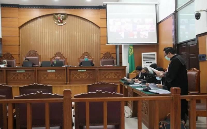 Penasihat Hukum terdakwa Ari Darmawan yakni pengemudi taksi daring dari LBH Mawar Saron Jakarta membacakan nota pembelaan terdakwa dalam sidang melalui video telekonferensi di Pengadilan Negeri Jakarta Selatan, Senin (27/4/2020). - Antara\n \n
