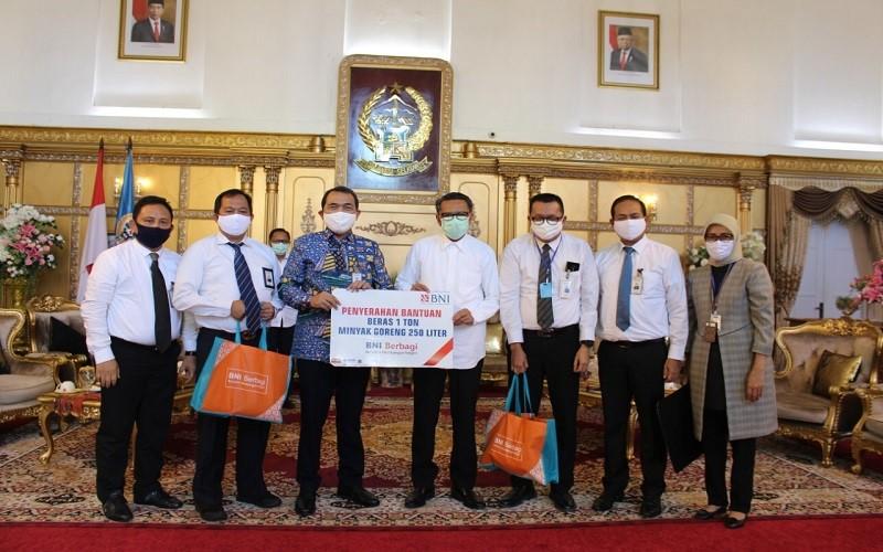 Pemimpin BNI Wilayah Makassar Faizal A. Setiawan menyerahkan bantuan secara simbolis kepada Gubernur Sulawesi Selatan Nurdin Abdullah - Istimewa