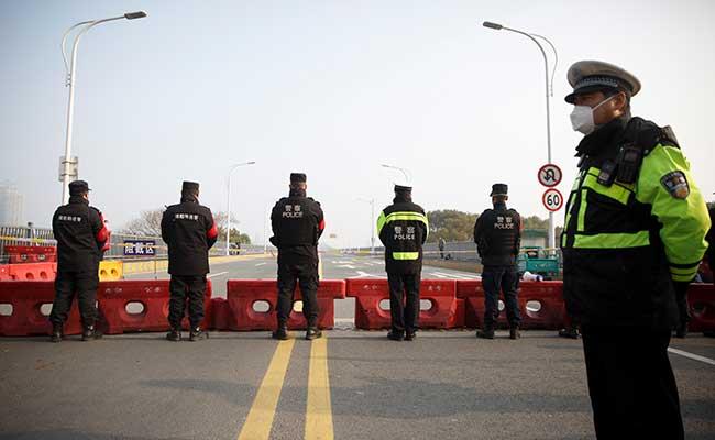 Polisi berjaga di pos pemeriksaan di Jembatan Sungai Jiujiang Yangtze yang melintasi dari provinsi Hubei ke Jiujiang di Provinsi Jiangxi, China, Jumat (31/1/2020). - Reuters/Thomas Peter
