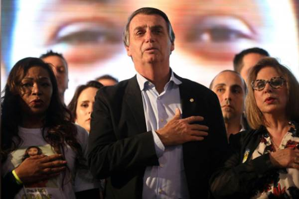 Bolsonaro mendengarkan lagu kebangsaan Brasil bersama sejumlah perempuan saat masa kampanye. - Reuters/Diego Vara.jpg