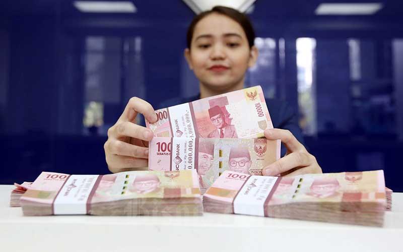 Karyawan menghitung uang pecahan Rp.100.000 di salah satu Bank yang ada di Jakarta, Senin (4/6). Bisnis - Abdullah Azzam