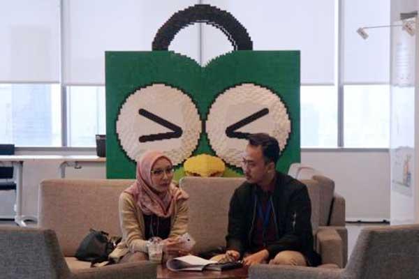 Karyawan beraktivitas di dekat logo Tokopedia di Jakarta, Selasa (28/1). Bisnis - Himawan L Nugraha