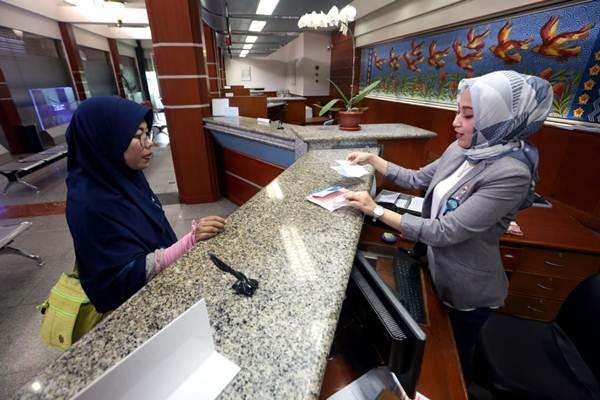 Karyawati melayani nasabah di PT Bank Pembangunan Daerah Jawa Barat dan Banten, Tbk. (Bank BJB) Kantor Cabang Utama Bandung, Jawa Barat, Rabu (20/6/2018). - Bisnis