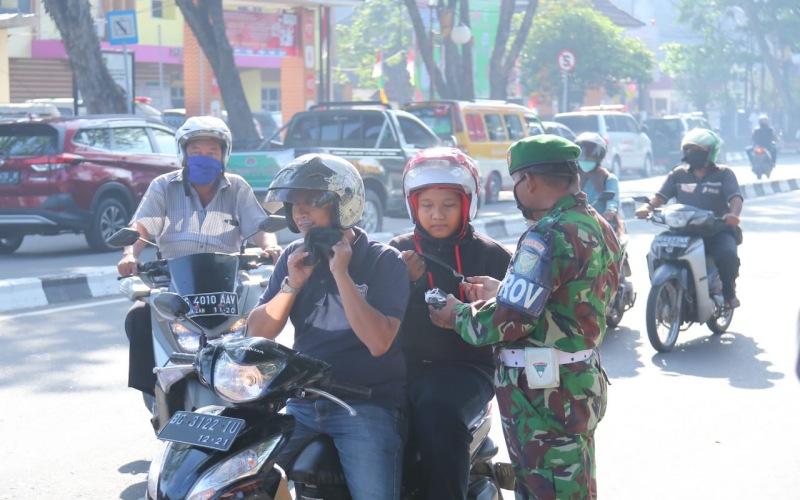 Ilustrasi / Petugas dari TNI memberikan masker dan mengedukasi pengendara motor terkait pencegahan wabah corona di Kota Palembang. istimewa