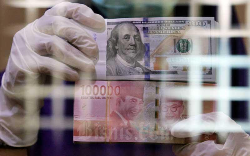 Karyawati menunjukan mata uang rupiah dan dolar Ameika Serikat di salah satu gerai penukaran mata uang asing di Jakarta, Kamis (2/4/2020). Bisnis - Arief Hermawan P
