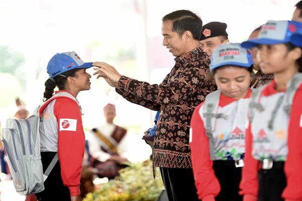 Presiden Joko Widodo berbincang dengan seorang peserta saat peringatan Hari Keluarga Nasional (Harganas) ke-23 di Kupang, Nusa Tenggara Timur, Sabtu (30/7). - Antara