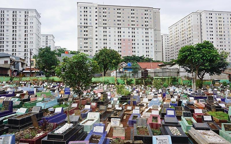 Deretan makam dengan latar gedung apartemen di Jakarta, Jumat (14/2/2020). Bisnis - Eusebio Chrysnamurti