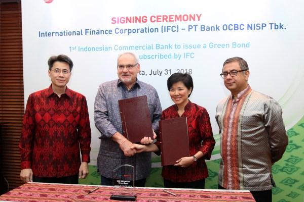 Presiden Direktur Bank OCBC NISP Parwati Surjaudaja (kedua kanan) bertukar dokumen dengan Direktur Eksekutif IFC Philippe Le Hourou (kedua kiri) disaksikan oleh Presiden Komisaris Bank OCBC NISP Pramukti Surjaudaja (kiri) dan Direktur IFC Asia Timur, dan Pasifik Vivek Pathak (kanan) di Jakarta, Selasa (31/7). /Bisnis - Emanuel B. Caesario