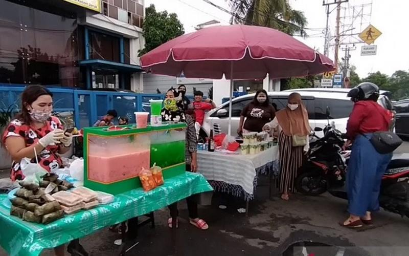 Pedagang takjil mengenakan masker dan sarung tangan saat berjualan di Jalan Panjang Kebon Jeruk, Jakarta Barat, Jumat (24/4/2020). - Antara\n\n