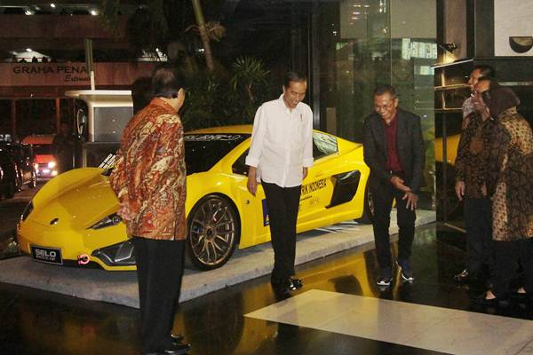 Presiden Joko Widodo (kedua kiri) bersama mantan Menteri BUMN Dahlan Iskan (ketiga kiri) berjalan usai melihat mobil listrik Selo saat berkunjung ke Surabaya, Jawa Timur, Minggu (8/10). - ANTARA/Moch Asim