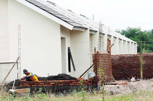 Pekerja sedang membangun tembok pembatas di salah satu proyek perumahan. Peserta BPJS Ketenagakerjaan atau BPJamsostek berkesempatan mencairkan dananya untuk dijadikan uang muka pembelian rumah pertama. - Bisnis