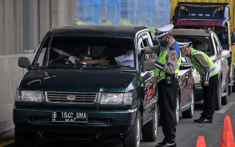 Petugas Kepolisian mengecek identitas mobil pribadi yang melintasi tol Jakarta-Cikampek di Cikarang Barat, Kabupaten Bekasi, Jawa Barat, Sabtu (9/5 - 2020). Direktorat Lalu Lintas Polda Metro Jaya akan menindak tegas kendaraan yang berupaya membawa penumpang keluar Jabodetabek dengan UU Nomor 22 tahun 2009 tentang Lalu Lintas dan Angkutan Jalan saat penerapan larangan mudik. ANTARA