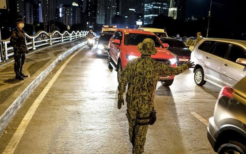 Anggota kepolisian Filipina menghentikan kendaraan di salah satu checkpoint di Makati-Jembatan Mandaluyong saat jam malam di Metro Manila (16/3/2020). - Veejay Villafranca/Bloomberg\n