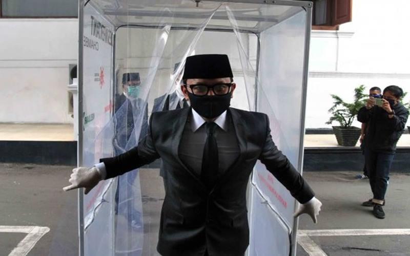Wali Kota Bogor Bima Arya keluar dari bilik disinfektan saat menuju ruang pelantikan pejabat struktural di lingkungan Pemerintah Kota Bogor di Ruang Paseban Sri Baduga, Balaikota Bogor, Jawa Barat, Selasa (28/4/2020). - Antara