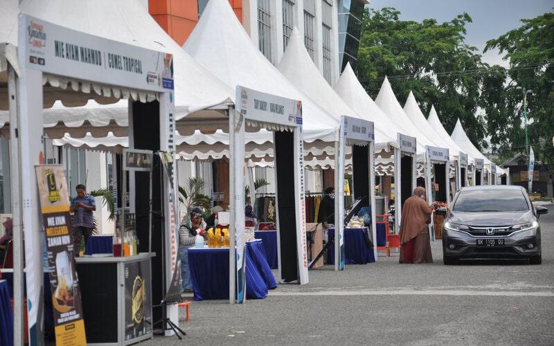 Sejumlah pelaku UMKM melayani pembeli dengan sistem 'Drive Thru' di kampung Ramadhan cegah Covid-19 Medan, Sumatera Utara, Selasa (5/5/2020). Kegiatan Kampung Ramadhan yang dilaksanakan oleh Pemerintah Provinsi Sumut tersebut merupakan salah satu pemberian stimulus kepada para pelaku UMKM dalam upaya memulihkan perekonomian akibat dampak pandemi virus Covid-19. - Antara/Septianda Perdana