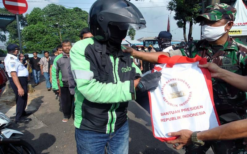 Pengemudi ojek daring menerima bantuan sembako dari Presiden Joko Widodo di Terminal Baranangsiang, Kota Bogor, Jawa Barat, Kamis (9/4/2020). Sebanyak 500 paket sembako dibagikan untuk warga yang terkena dampak ekonomi akibat wabah pandemi virus Corona (COVID-19) di Kota Bogor. ANTARA FOTO - Arif Firmansyah