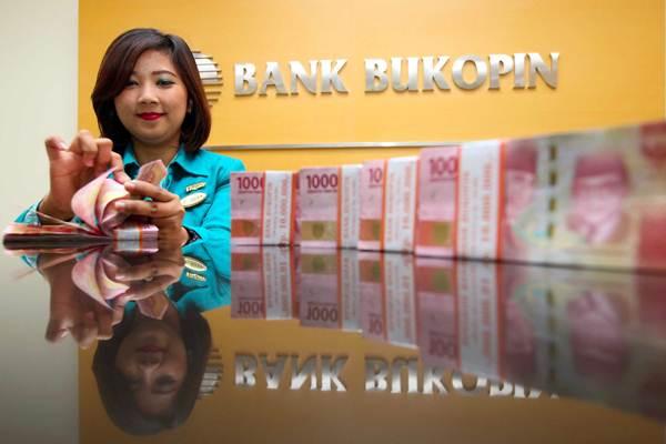 Karyawati menghitung uang rupiah, di kantor Cabang Bank Bukopin di Jakarta, Senin (9/4/2018). - JIBI/Abdullah Azzam