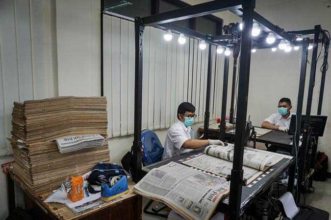 Pegawai bagian konservasi preservasi melakukan proses digitalisasi halaman koran di Monumen Pers Nasional, Solo, Jawa Tengah, Senin (11/2/2019). - ANTARA/Mohammad Ayudha