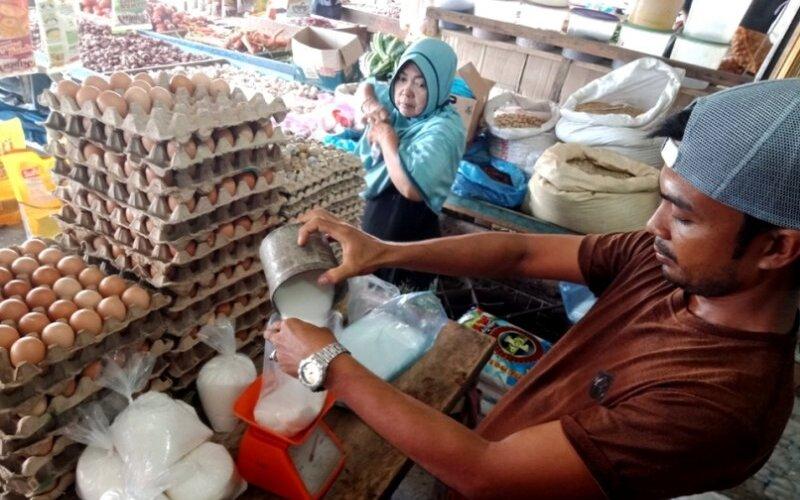 Seorang pedagang di Pasar Bina Usaha Meulaboh, Kabupaten Aceh Barat, mengecer gula pasir ke dalam bentuk kemasan satu kilogram sebelum dijual ke konsumen, Minggu (5/4/2020). - Antara/Teuku Dedi Iskandar\n