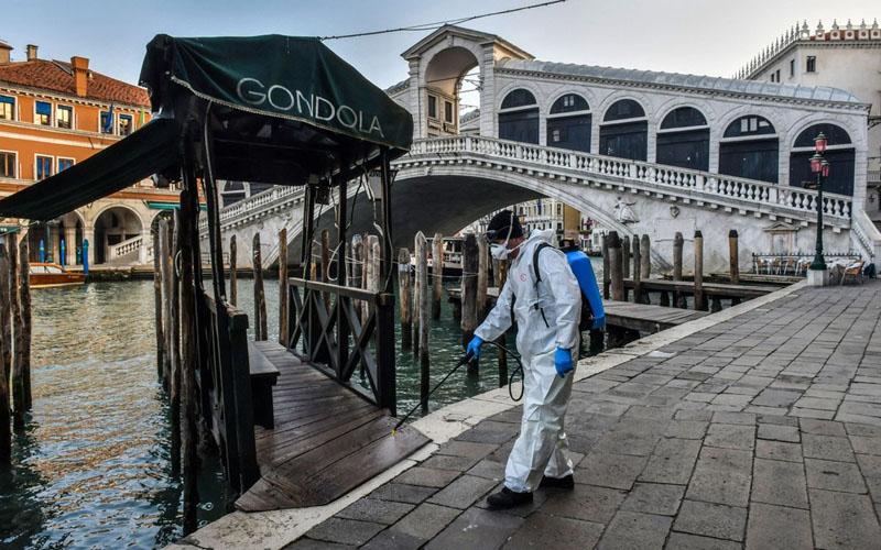 Seorang pria menyemprotkan disinfektan untuk mematikan virus corona di kota air Venesia, Italia. - Bloomberg