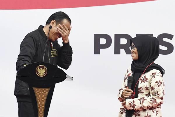 Presiden Joko Widodo (kiri) tertawa saat berbincang dengan penerima kartu Program Keluarga Harapan (PKH) di sela-sela sosialisasi kepada penerima dan pendamping di Gelanggang Remaja Jakarta Timur, Jakarta, Senin (3/12/2018). - ANTARA/Puspa Perwitasari
