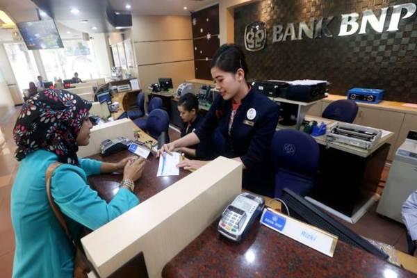 Petugas melayani nasabah yang melakukan transaksi perbankan di Kantor Pusat PT Bank Nusantara Parahyangan Tbk. (Bank BNP) di Bandung, Jawa Barat, Senin (8/1). - JIBI/Rachman