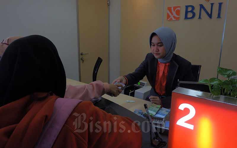 Karyawan melayani nasabah di salah satu kantor cabang milik PT Bank Negara Indonesia (Persero) Tbk. yang ada di Jakarta, Senin (25/2). Bisnis - Nurul Hidayat