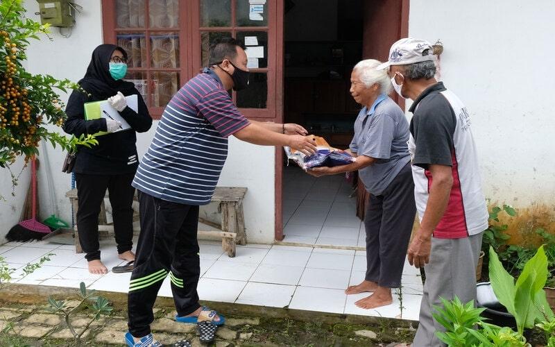 Petugas Jaring Pengaman Sosial (JPS) swadaya tingkat desa memberikan bantuan sembako kepada warga terdampak Covid-19 di Perumahan Candi Asri, Kedu, Temanggung, Jawa Tengah, Rabu (8/4/2020). Warga setempat secara swadaya melakukan iuran yang hasilnya disumbangkan kepada warga terdampak Covid-19 berupa sembako dan hand sanitizer. - Antara/Anis Efizudin\n