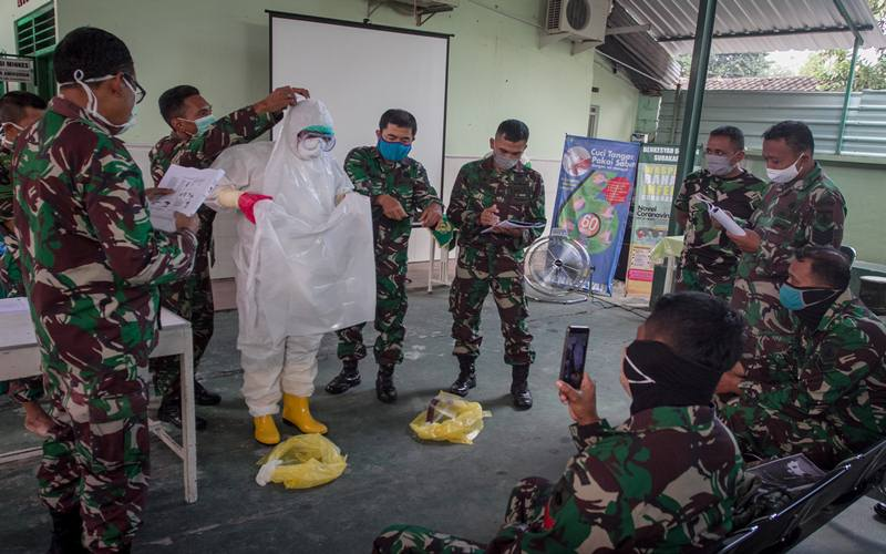 Anggota TNI Korem 074/Warastratama mempraktekan prosedur memakai dan melepas alat pelindung diri (APD) saat pelatihan menggunakan APD di Rumah Sakit Tentara (RST) Slamet Riyadi, Solo, Jawa Tengah, Senin (13/42020). Kegiatan pelatihan yang diikuti perwakilan Kodim Soloraya tersebut untuk memberikan pengetahuan cara penggunaan APD dengan benar dalam rangka menyiapkan personil TNI membantu penanganan pemakaman jenazah suspect COVID-19. ANTARA FOTO - Mohammad Ayudha