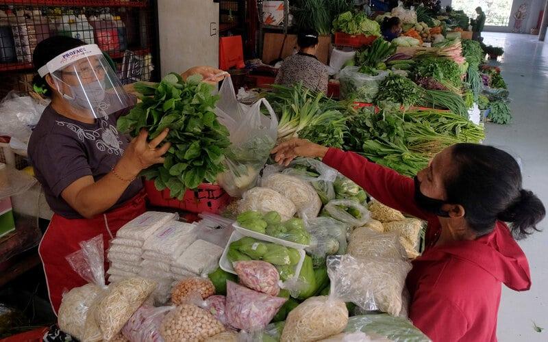 Pedagang menggunakan alat pelindung wajah saat melayani pembeli pada hari pertama Pembatasan Kegiatan Masyarakat (PKM) di Pasar Badung, Denpasar, Bali, Jumat (15/5/2020). Pedagang di pasar-pasar tradisional di Denpasar diwajibkan menggunakan alat pelindung wajah dalam penerapan PKM tersebut untuk menghentikan penyebaran Covid-19. - Antara/Nyoman Hendra Wibowo