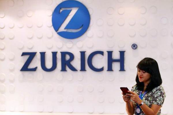 Karyawati mengoperasikan ponsel pintar di dekat logo Zurich Insurance Indonesia di Jakarta, Senin (29/5). - JIBI/Dwi Prasetya