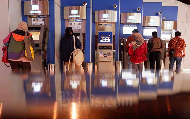 Nasabah melalukan transaksi lewat mesin anjungan tunai mandiri (ATM) milik PT Bank Central Asia Tbk (BCA) di Jakarta, Senin (9/7/2018). Bisnis - Nurul Hidayat