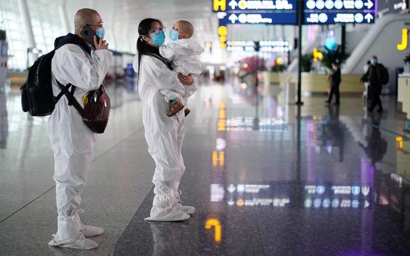 Sepasang orang tua beserta bayinya menggunakan pakaian pelindung saat berada di Bandara Internasional Tianhe Wuhan, ibu kota Provinsi Hubei, China, yang menjadi pusat wabah virus corona jenis baru COVID-19 pada Jumat (10/4/2020)./Antara - Reuters