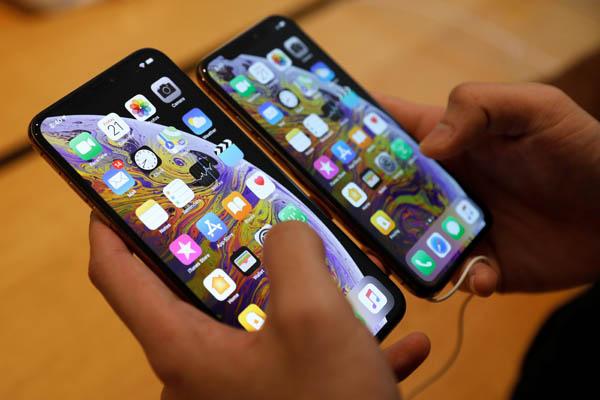 Seorang pembeli mencoba membandingkan ukuran iPhone XS Max dan iPhone XS di gerai Apple Singapura Jumat (21/9/2018). - Reuters/Edgar Su