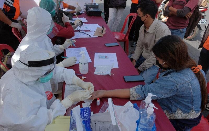 Tim medis melakukan tes cepat Covid-19 terhadap warga dalam penerapan Pembatasan Kegiatan Masyarakat (PKM) di pos pantau perbatasan Penatih, Denpasar, Bali, Sabtu (16/5/2020). Tes cepat yang digelar di delapan titik pos pantau perbatasan Denpasar tersebut menyasar warga yang datang dari kawasan zona merah, luar pulau Bali, pekerja yang bertugas keliling dan bagi warga yang suhu tubuhnya melebihi 38 derajat celcius sebagai upaya menghentikan penyebaran Covid-19. - Antara/Nyoman Hendra Wibowo