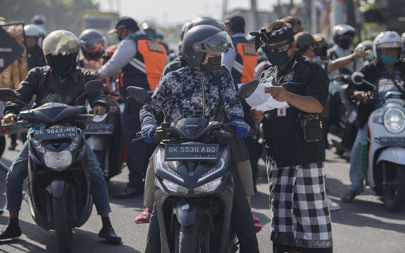 Anggota satuan pengamanan adat Bali atau Pecalang memeriksa surat jalan seorang pengendara saat hari pertama penerapan Pembatasan Kegiatan Masyarakat (PKM) di pos pantau perbatasan Biaung, Denpasar, Bali, Jumat (15/5/2020). - Antara