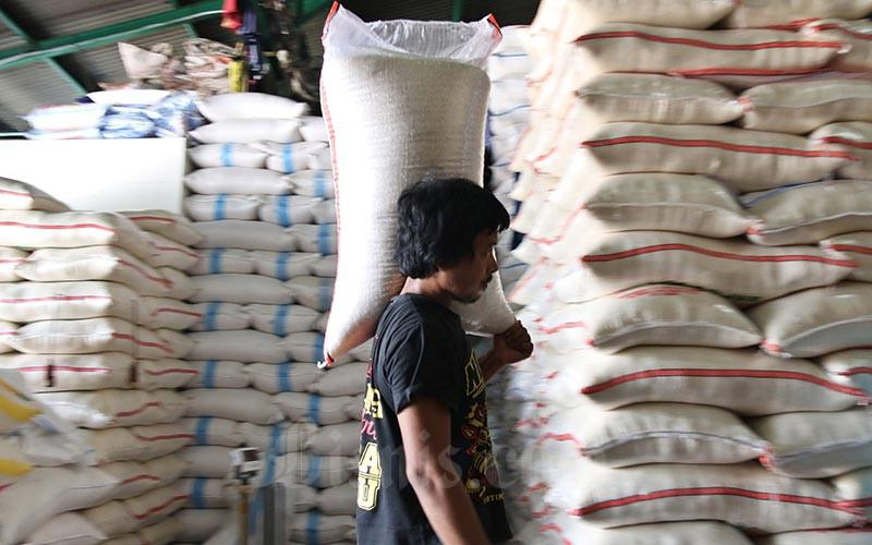 Buruh mengangkut karung beras. Bisnis - Eusebio Chrysnamurti