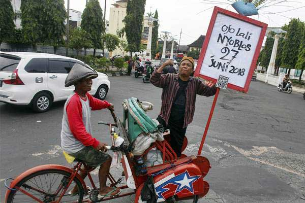 Warga mengusung poster bertuliskan Ojo Lali Nyoblos di Jalan Jendral Sudirman, Solo, Jawa Tengah, Selasa (26/6/2018). - ANTARA/Maulana Surya