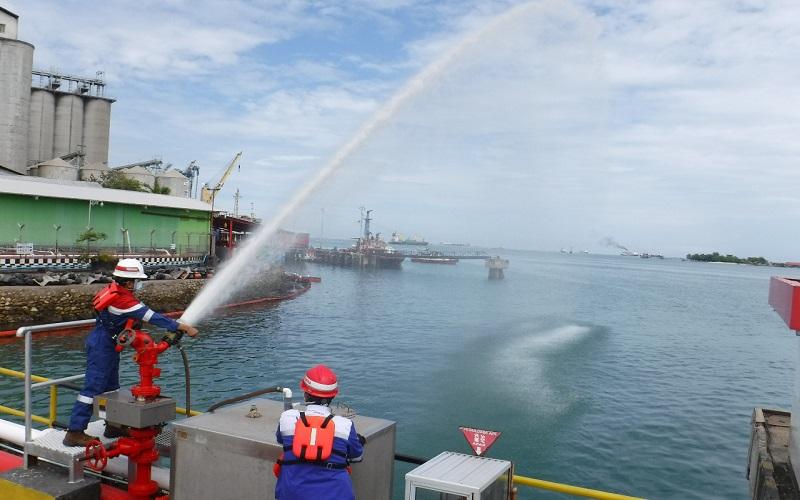 Petugas dari PT. Pertamina membersihkan tumpahan minyak di pesisir pantai Makassar - Istimewa
